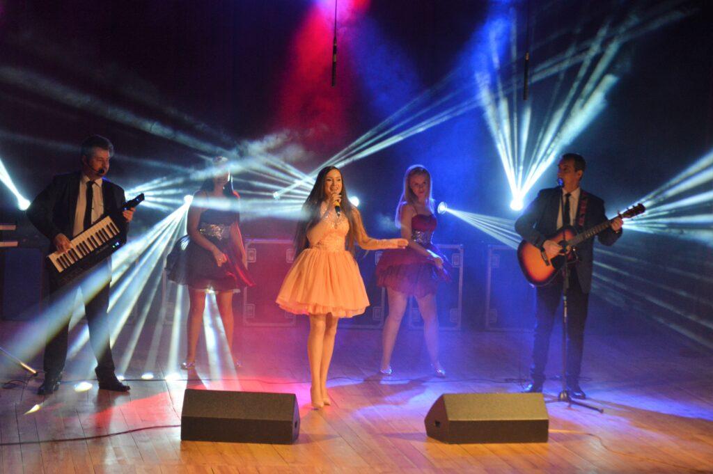 Koncert zespołu na kolorowo oświetlonej scenie