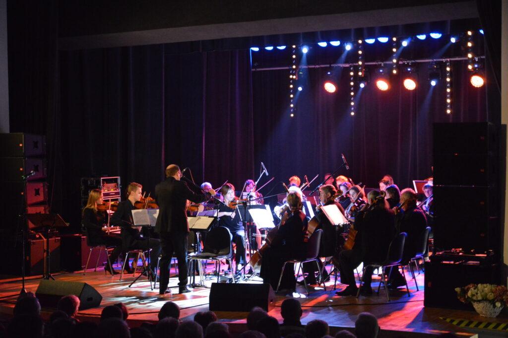 Koncert orkiestry na kolorowo oświetlonej scenie