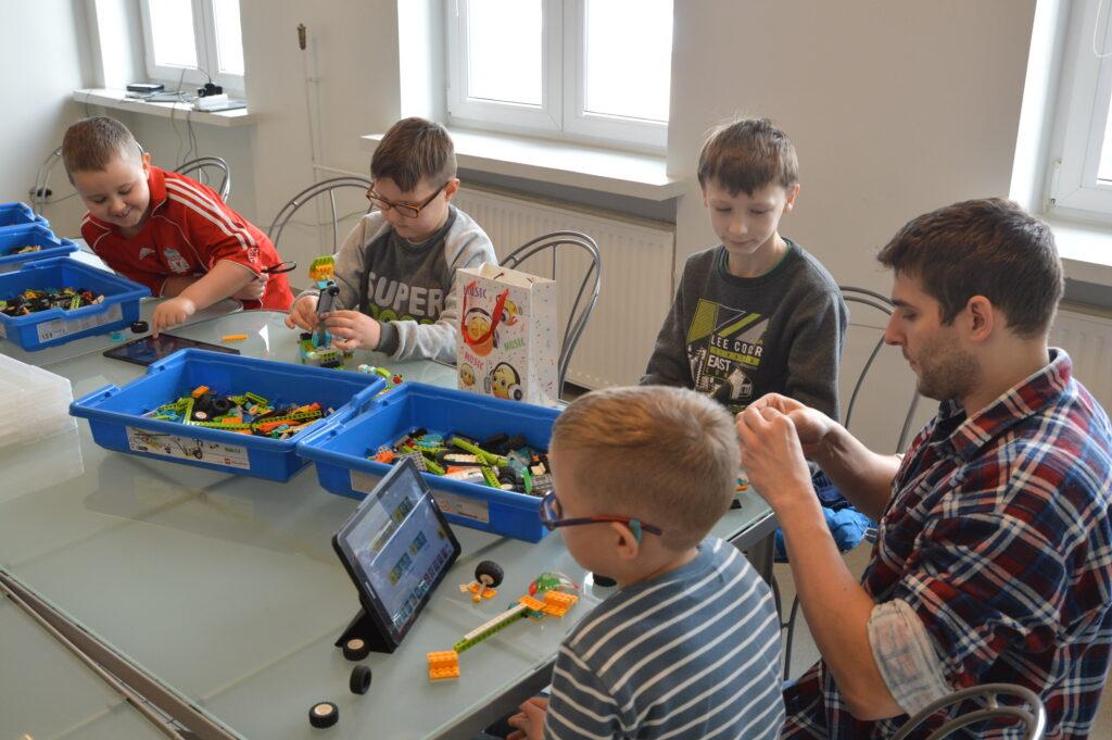 Dzieci z instruktorem podczas zajęć z robotyki